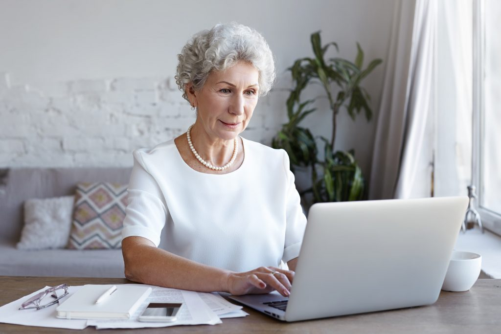 Elderly woman paying bill on computer at home